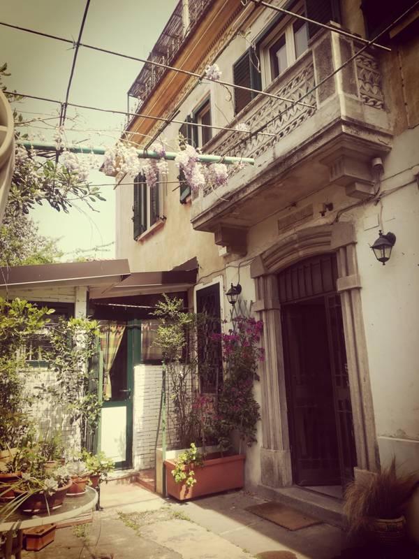 Ingresso di palazzina con balcone, cortile con fiori