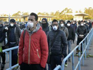 Covid-19 La fine del Mondo che conosciamo, Persone in fila a distanza di un metro con la mascherina