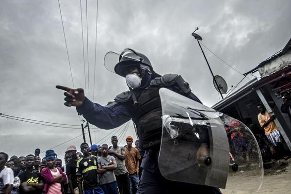 Poliziotto in tenuta antisommossa si rivolge a una folla di manifestanti nel quartiere di West Point a Monrovia, dopo l'entrata in vigore della quarantena nel tentativo di contenere la diffusione di Ebola nel 2014.